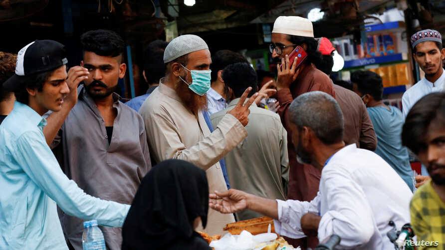 FILE PHOTO: A man wearing a protective face mask as he gestures while shopping amid the rush of people outside an electronics…
