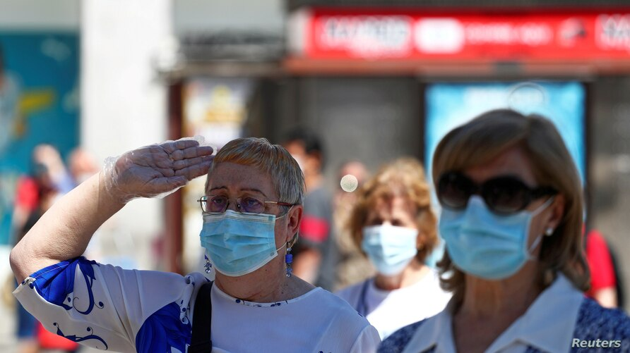 FILE PHOTO: A woman wearing a protective face mask salutes as people hold a minute of silence during the last day of the…