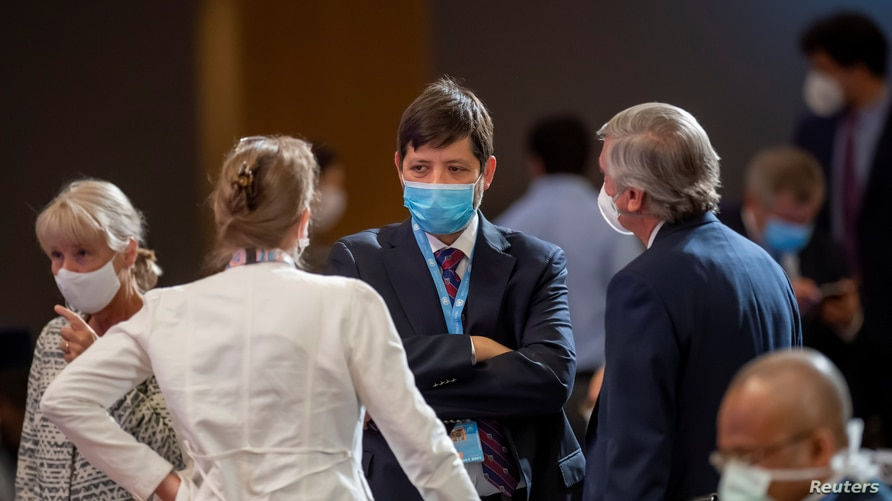 Delegates wearing protective face masks talk during an urgent debate on current racially inspired human rights violations,…
