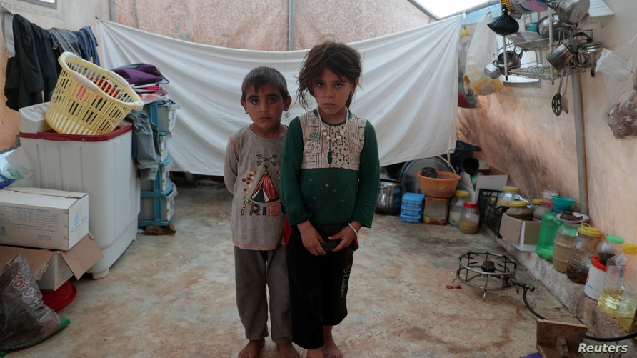 Jumana and Farhan al-Alyawi, 8-year-old displaced Syrian twins from east Idlib, pose for a picture in a tent at Atmeh camp,…