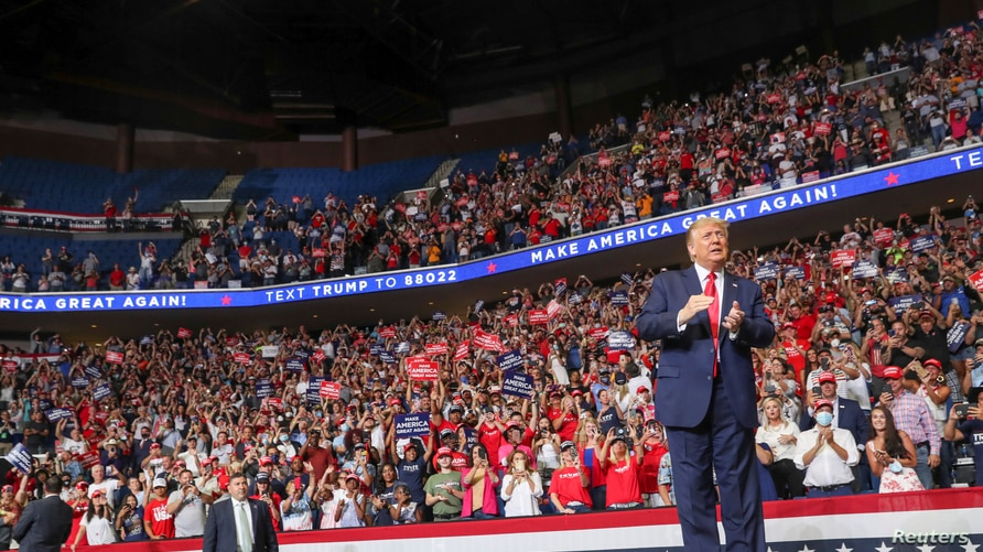 US President Donald Trump reacts to the crowd as he arrives onstage at his first re-election campaign rally in several months.