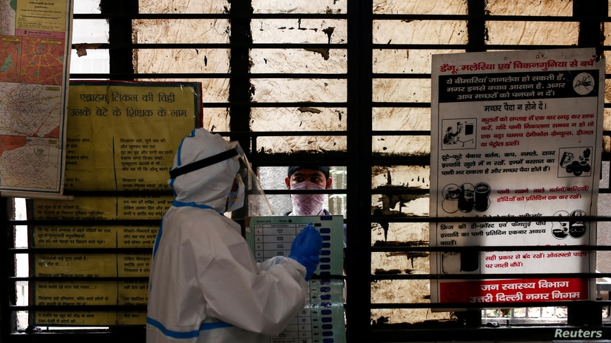 A medical worker gets ready to collect a sample from a man at a school turned into a centre to conduct tests for the…
