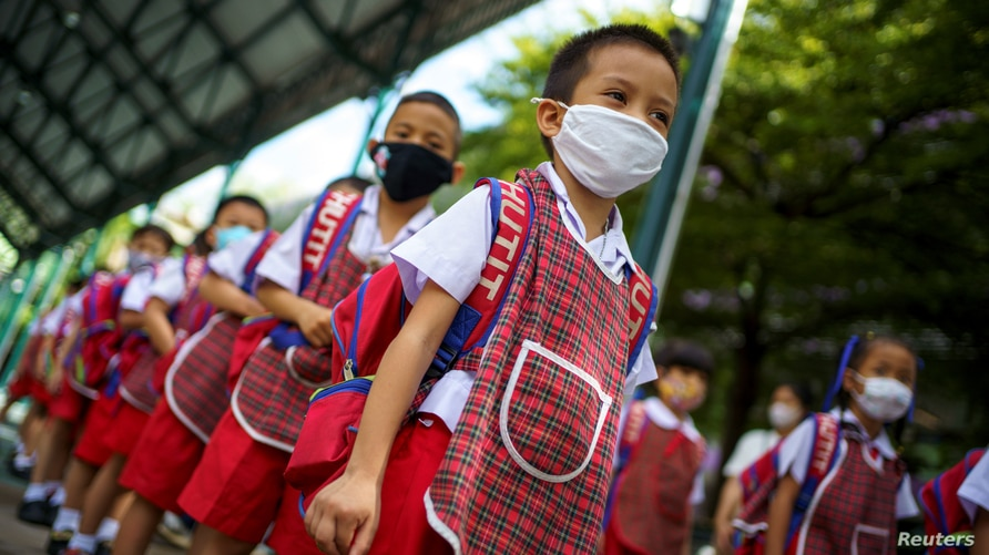 Kindergarten students from the Wichuthit school wearing face masks attend a rehearsal social distancing and measures to prevent…