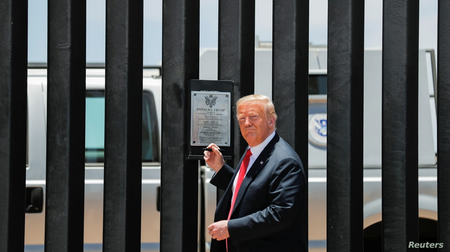 U.S. President Donald Trump prepares to autograph a plaque commemorating the construction of the 200th mile of border wall…