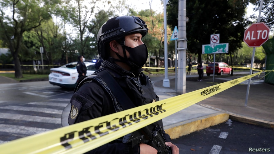 A police officer stands behind a cordon tape at an area where a shooting took place in Mexico City, Mexico, June 26, 2020…