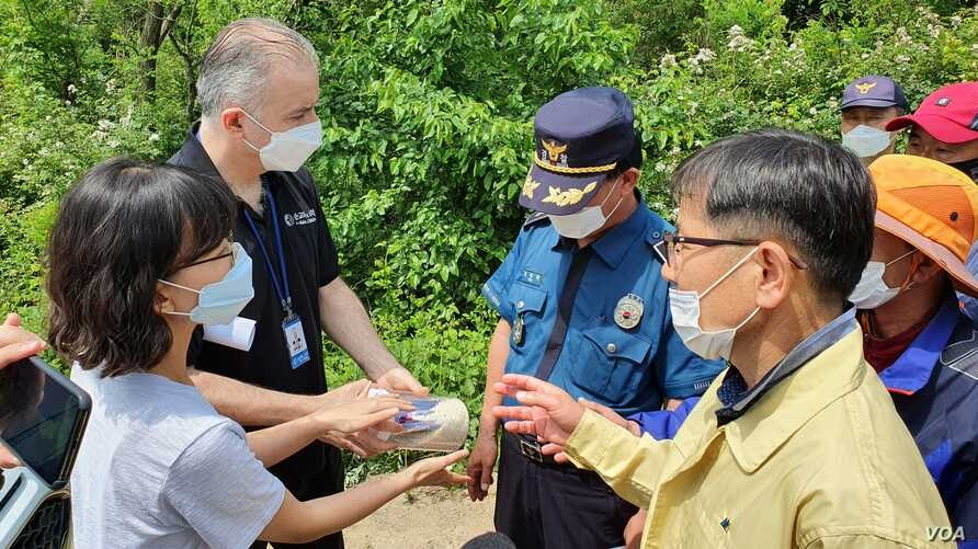 Local police and other officials prevent Voice of the Martyrs Korea, a North Korea-focused NGO, from conducting a launch of rice bottles filled with aid and Bibles toward North Korea, in Incheon, South Korea,  June 5, 2020. (William Gallo/VOA)