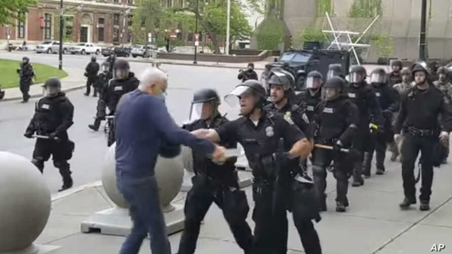 In this image from video provided by WBFO, a Buffalo police officer appears to shove a man who walked up to police Thursday.
