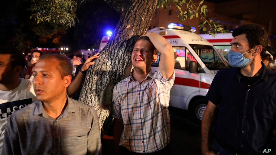 A man whose relative is on staff at Sina Athar Clinic weeps after its explosion, outside the clinic in Tehran, Iran, early Wednesday, July 1, 2020. Iranian state TV says an explosion from a gas leak in a medical clinic in northern Tehran has killed multiple people.