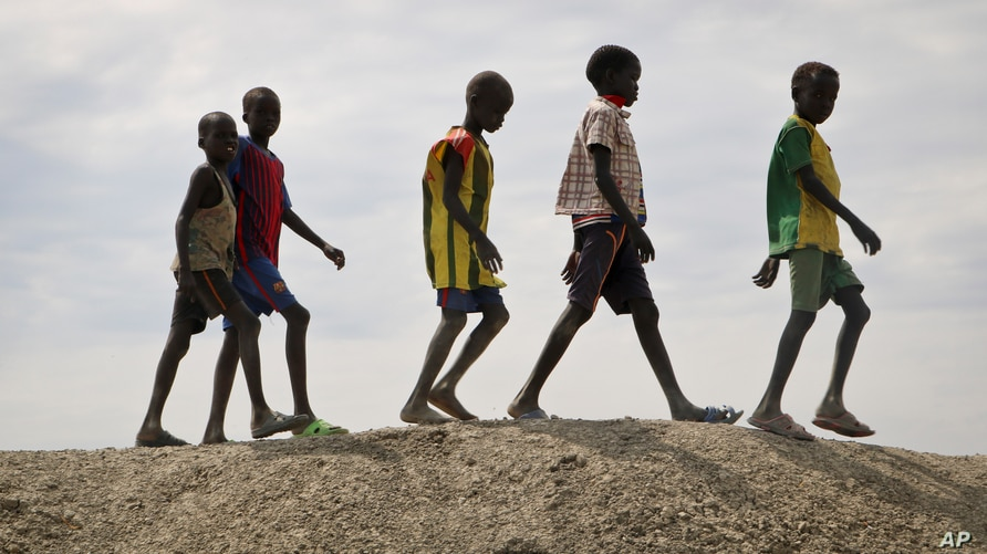 In this photo taken Dec. 9, 2018, a group of youths walk on top of a small hill of dirt in the United Nations protection of civilians site in Bentiu, South Sudan.
