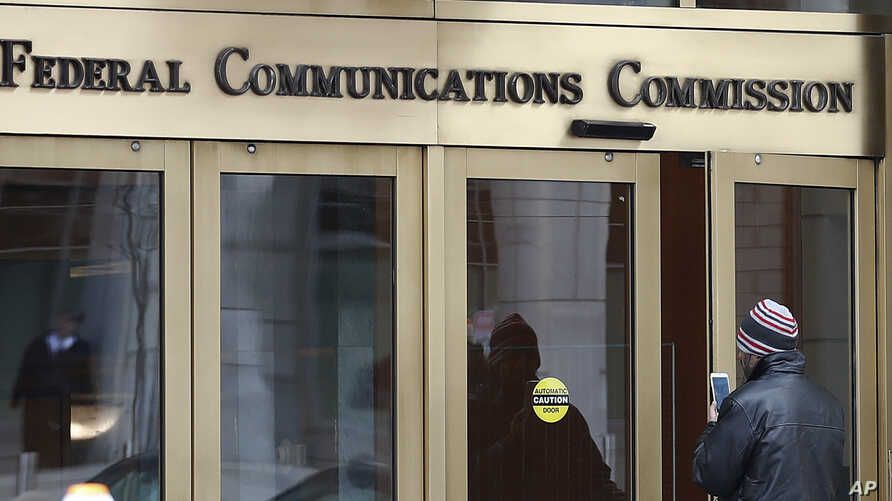 FILE - In this Thursday, Dec. 14, 2017, file photo, a person with a smartphone enters the Federal Communications Commission…