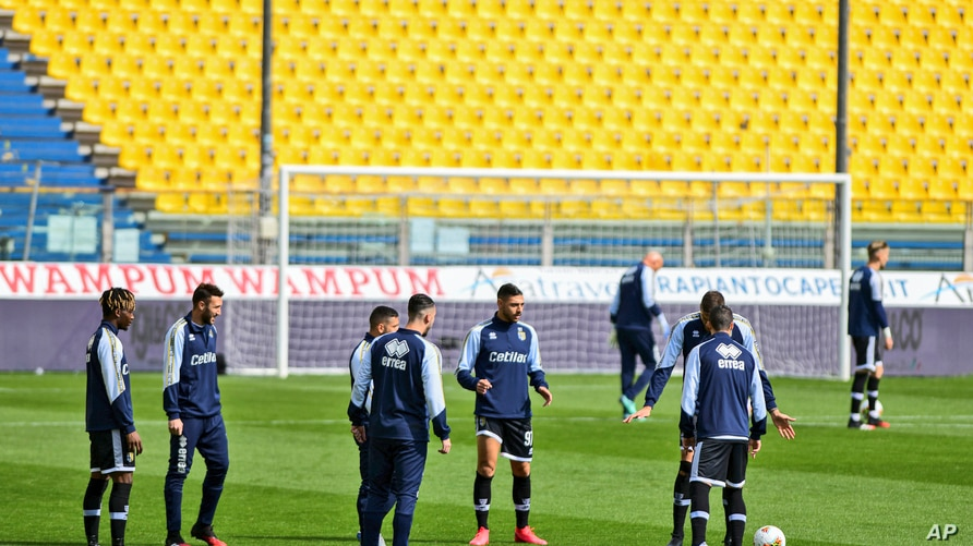 Parma's players warm up on the field moments before a Serie A soccer match between Parma and Spal was scheduled to be played, in Parma, northern Italy, March 8, 2020.