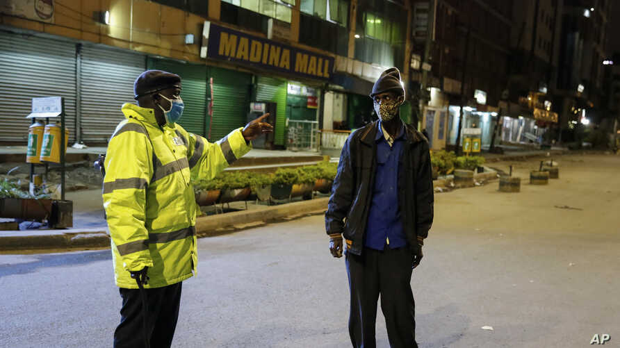 A Kenyan police officer stops a man who was heading home past the start of the daily dusk-to-dawn curfew in the Eastleigh area.