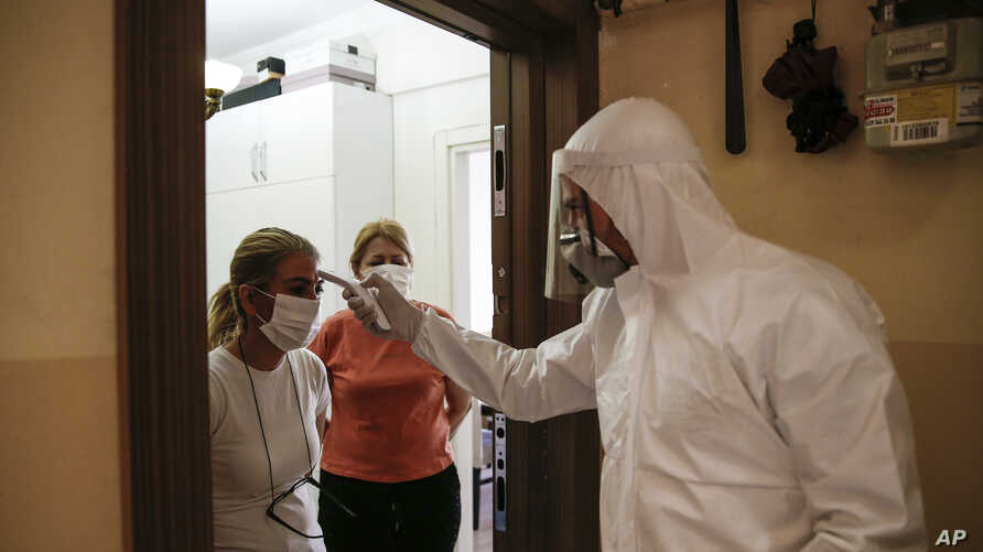 In this Friday, May 15, 2020 photo, a contact tracer with Turkey's Health Ministry's coronavirus contact tracing team, clad in…