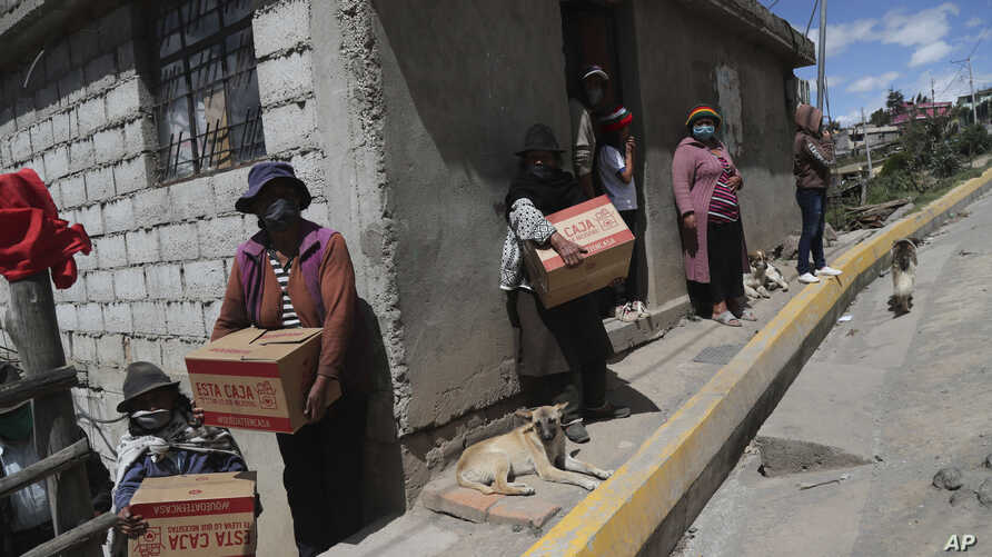 Residents wearing protective face masks hold food boxes distributed by the government during a lockdown to contain the spread…