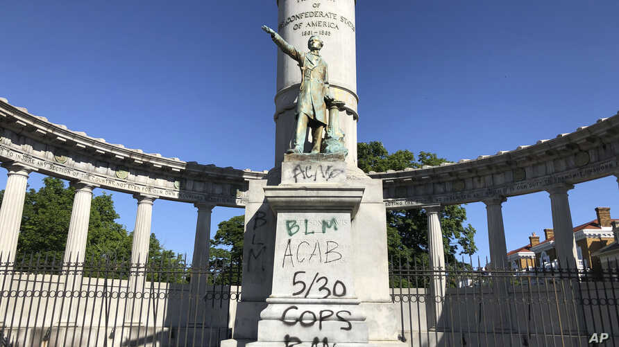 A monument to Confederate President Jefferson Davis in Richmond, Va., is covered with graffiti on Sunday, May 31, 2020, after overnight protests over the death of George Floyd.