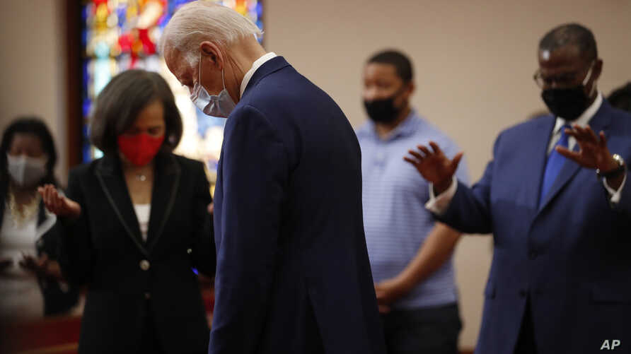 Democratic presidential candidate, former Vice President Joe Biden bows his head in prayer during a visit to Bethel AME Church.
