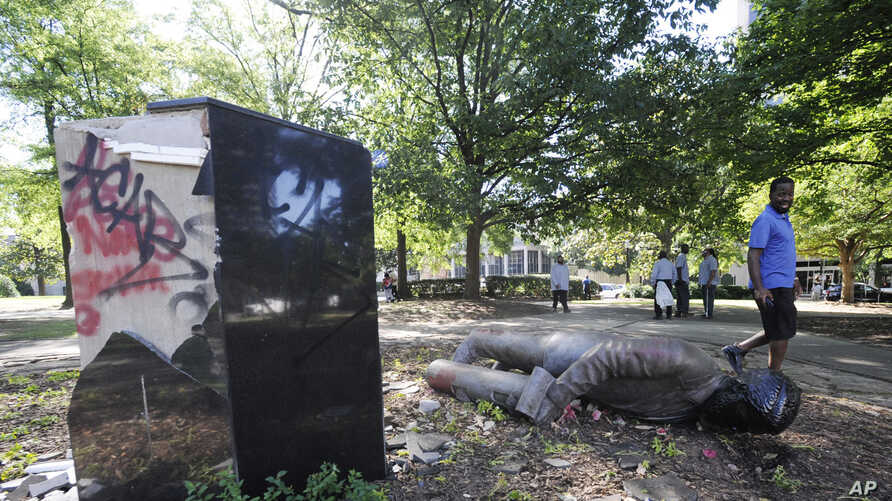 ADDS INFORMATION ON STATUE - An unidentified man walks past a toppled statue of Charles Linn, a city founder who was in the…