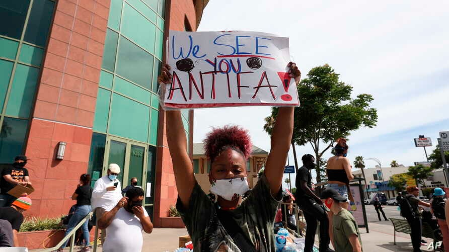 A woman holds a sign addressing antifa at a protest in Los Angeles on June 1, 2020, over the death of George Floyd, who died May 25 in Minneapolis.