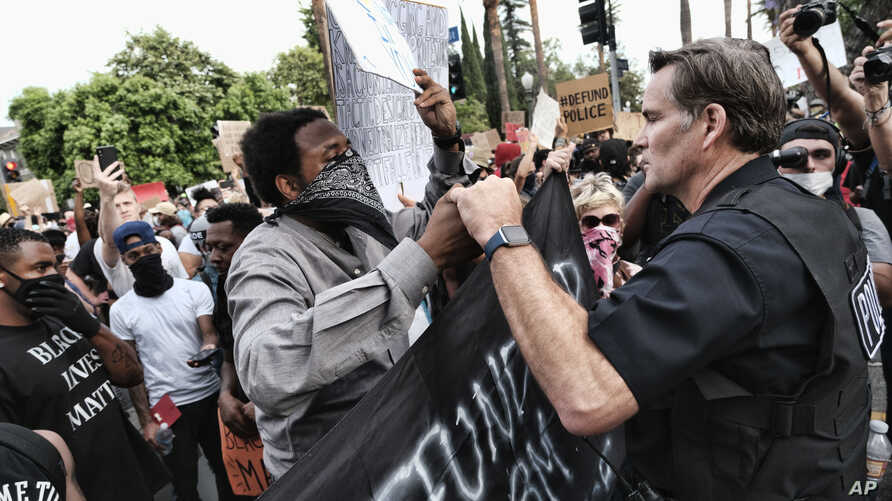 "Los Angeles Commander Cory Palka, right reaches out and offers a handshake to a ""Black Lives Matter"" protester"