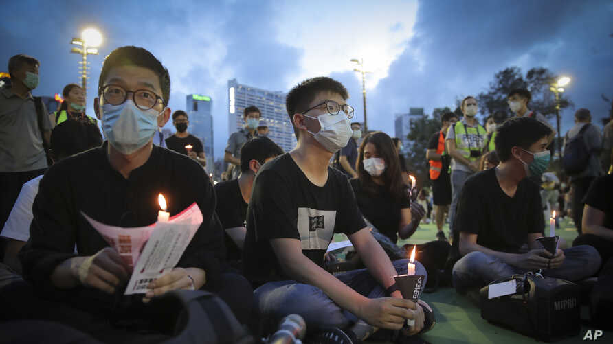 Hong Kong democracy activist Joshua Wong, center, holds a candle as he joins others for a vigil