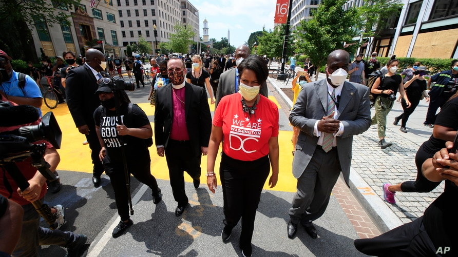 District of Columbia Mayor Muriel Bowser walks on the street leading to the White House after the words Black Lives Matter were painted in enormous bright yellow letters on the street by city workers and activists, June 5, 2020, in Washington.