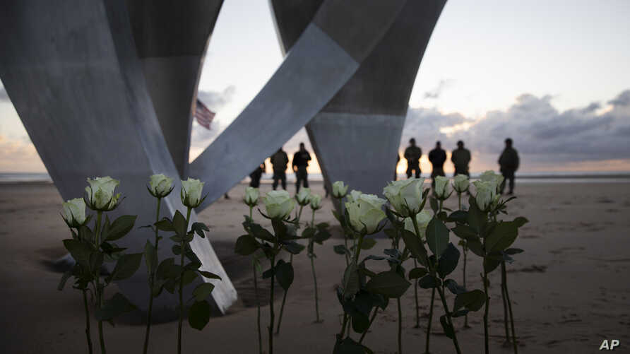 Men in a vintage US WWII uniforms stand behind flowers left at Les Braves monument after a D-Day 76th anniversary ceremony in Saint Laurent sur Mer, Normandy, France, June 6, 2020.