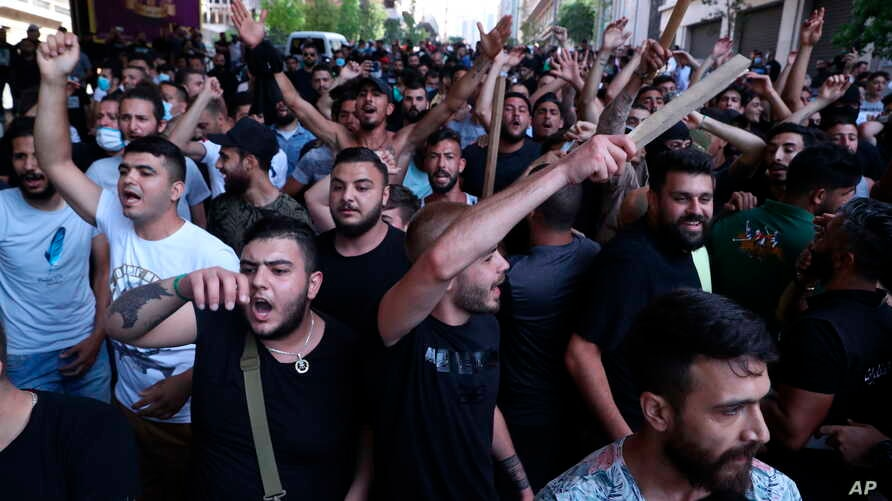 Shiite Hezbollah and Amal Movement groups stand in front of Lebanese army as they shout slogans against anti-government protesters, in downtown Beirut, Lebanon, Saturday, June 6, 2020.