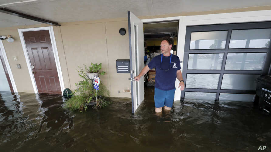 Rudy Horvath walks out of his home, a boathouse in the West End section of New Orleans, as it takes on water a from storm surge…