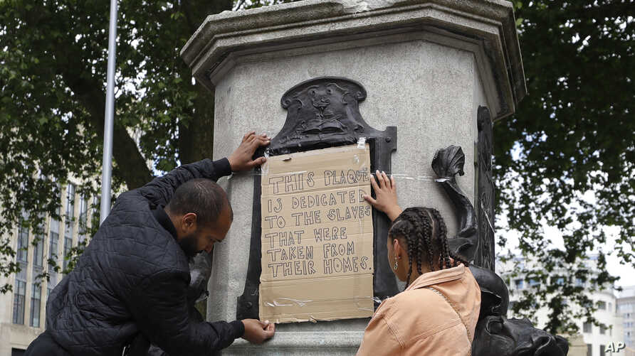 A banner is taped over the inscription on the pedestal of the toppled statue of Edward Colston in Bristol, England, Monday,…