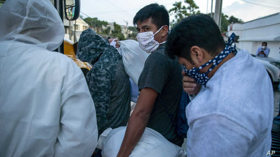 Guatemalans deported from the U.S., wearing a mask as a precaution against the spread of the new coronavirus, line up to board a bus after arriving at La Aurora airport in Guatemala City, June 9, 2020.