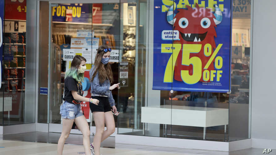 Two girls walk past a store with sale signs displayed at Great Lakes Mall, Wednesday, June 10, 2020, in Mentor, Ohio. Sales for…