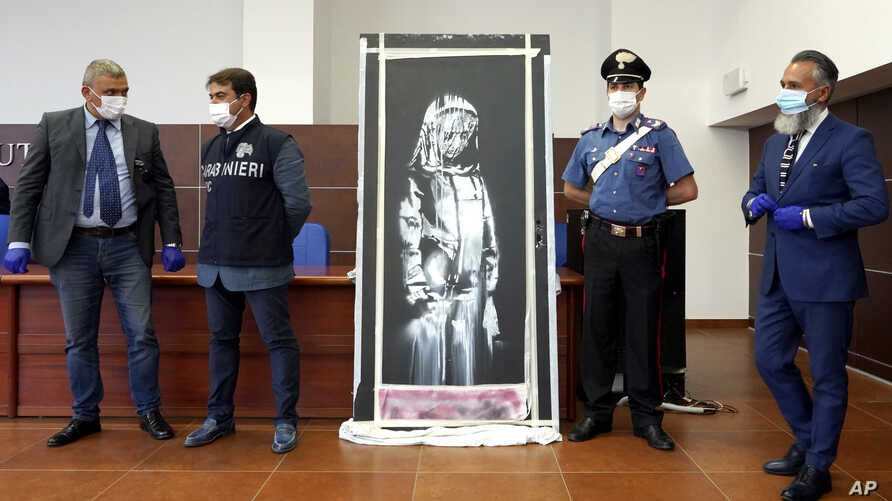 Italian authorities unveil a stolen artwork painted by the British artist Banksy as a tribute to the victims of the 2015 terror attacks at the Bataclan music hall in Paris, during a press conference in L' Aquila, Italy, June 11, 2020.