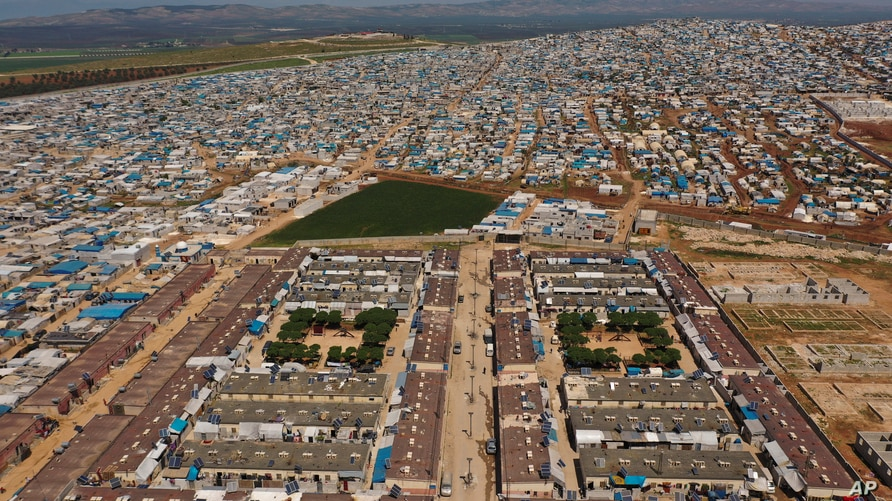 FILE - This April 19, 2020 photo file photo, shows a large refugee camp on the Syrian side of the border with Turkey, near the…