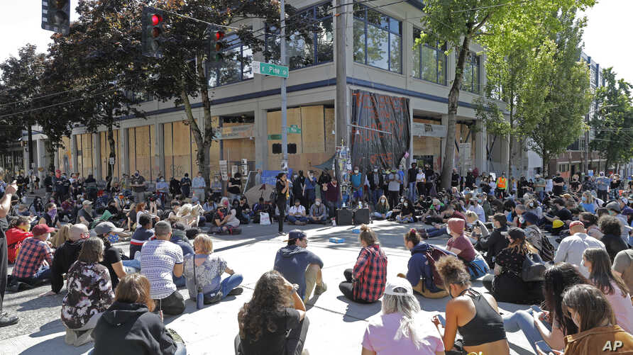 Protesters listen to a speaker as they sit in front of the Seattle Police Department East Precinct building