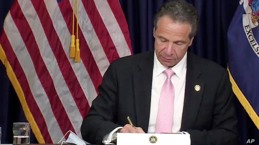 In this photo made from video provided by the office of New York Governor Andrew M. Cuomo, Gov. Cuomo, signs into law, Friday,…