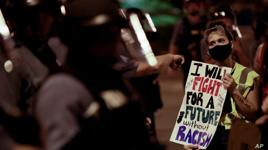 A protester confronts a line of police in riot gear early Thursday, June 4, 2020, in Kansas City, Mo., after a unity march to…