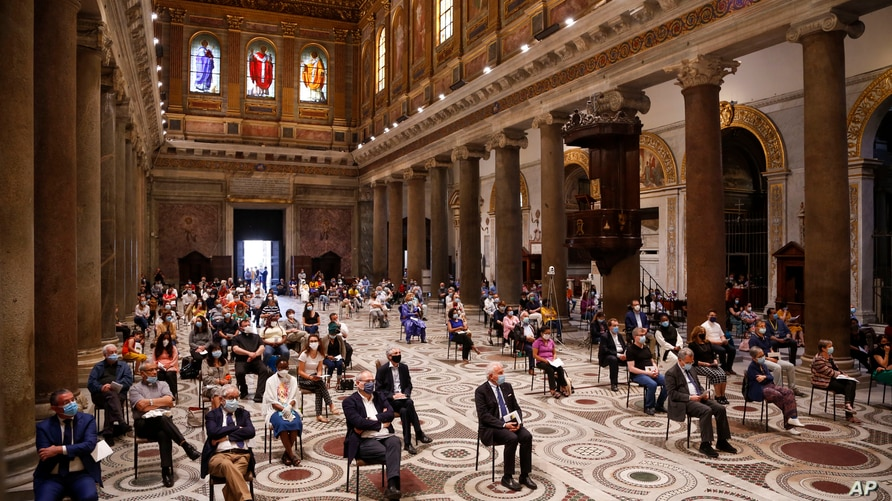 People attend a vigil prayer for the deceased would be migrants in Rome's Basilica of Our Lady in Trastevere on the World Day of Migrants, June 18, 2020.