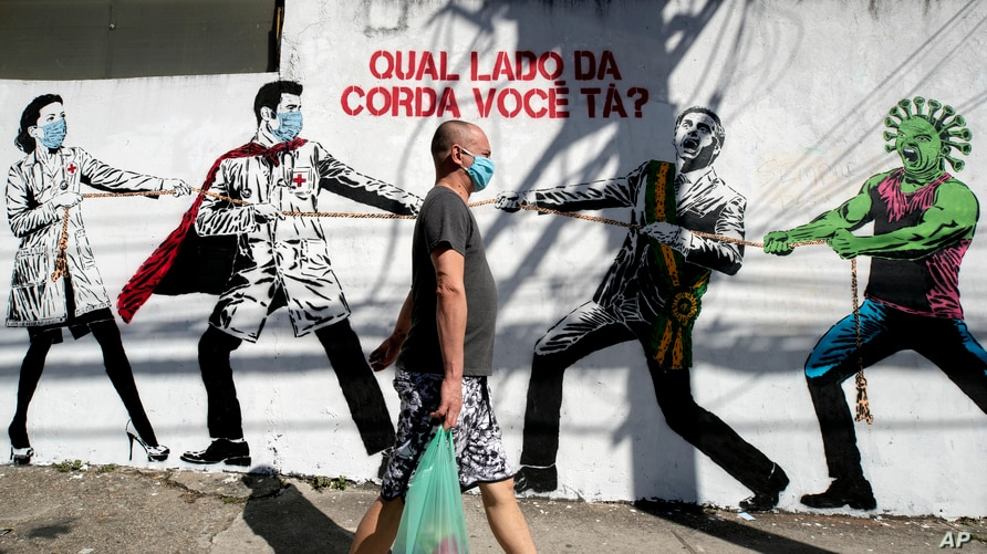 A man, wearing a protective face mask as a measure to curb the spread of the new coronavirus, walks past a mural depicting a…