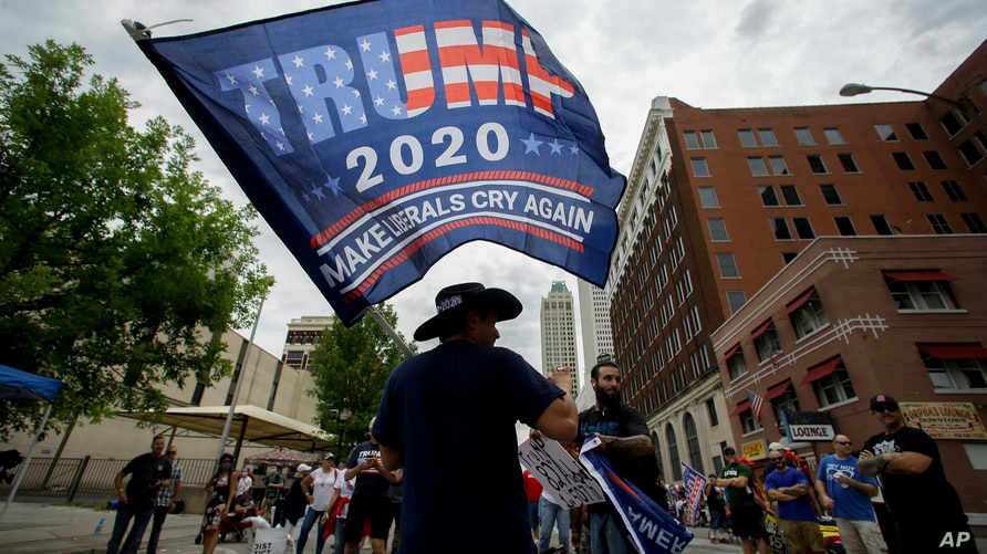 A supporter waves a flag prior to a campaign rally for President Trump at the BOK Center in Tulsa, Okla., Saturday, June 20, 2020. (AP Photo/Charlie Riedel)