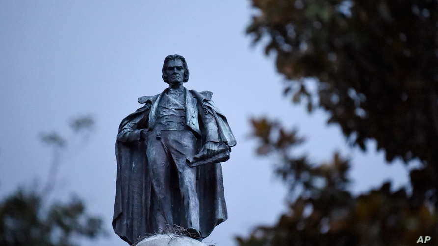A 100-foot monument to former U.S. vice president and slavery advocate John C. Calhoun towers over a downtown square Tuesday, June 23, 2020, in Charleston, S.C.