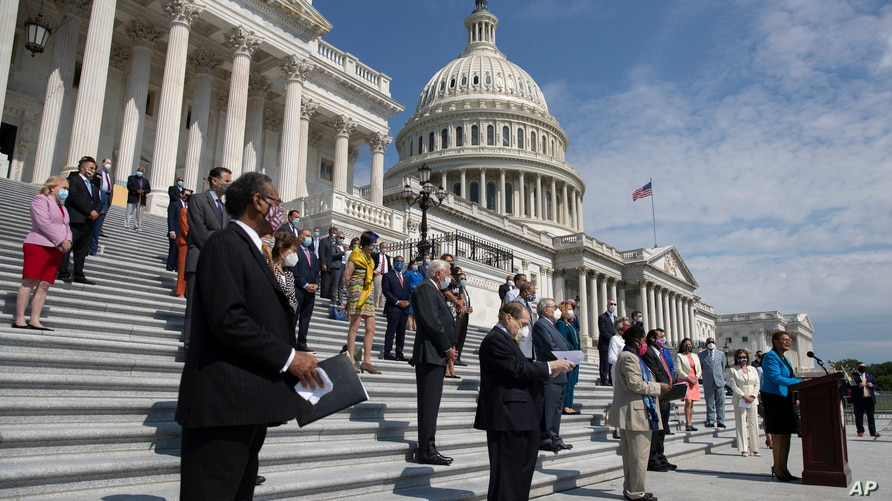 Rep. Karen Bass joined by House Speaker Nancy Pelosi, and other House Democrats spaced for social distancing, speaks during a news conference on the House East Front Steps on Capitol Hill in Washington, June 25, 2020.