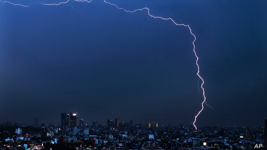 A bolt of lightning strikes during an early morning storm in Mexico City, June 22, 2020.