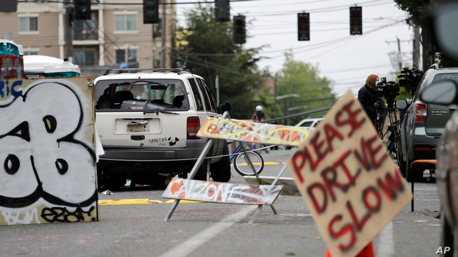 A car with broken windows and bullet holes that was involved in a shooting sits in the street Monday, June 29, 2020, in Seattle…