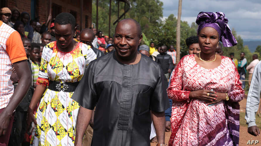 Evariste Ndayishimiye (2nd R), Burundi's Presidential candidate of the ruling party CNDD-FDD, and his wife Angelique Ndayubaha (R) arrive to vote during the presidential and general elections at the Bubu Primary school in Giheta, May 20, 2020.
