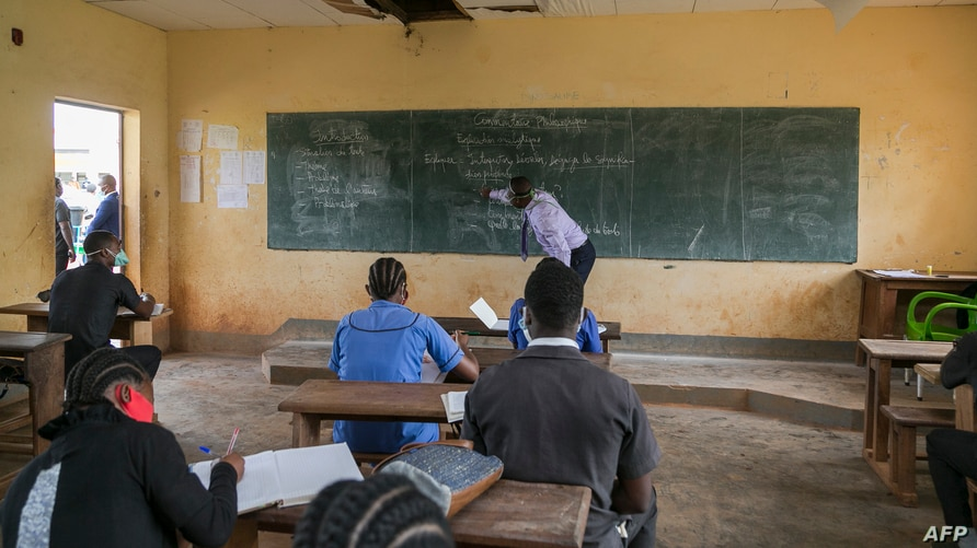 FILE - A teacher wearing a face mask to protect against the coronavirus writes on a blackboard at the Technical High School of Nkol-Bisson in Yaounde, Cameroon, June 1, 2020.