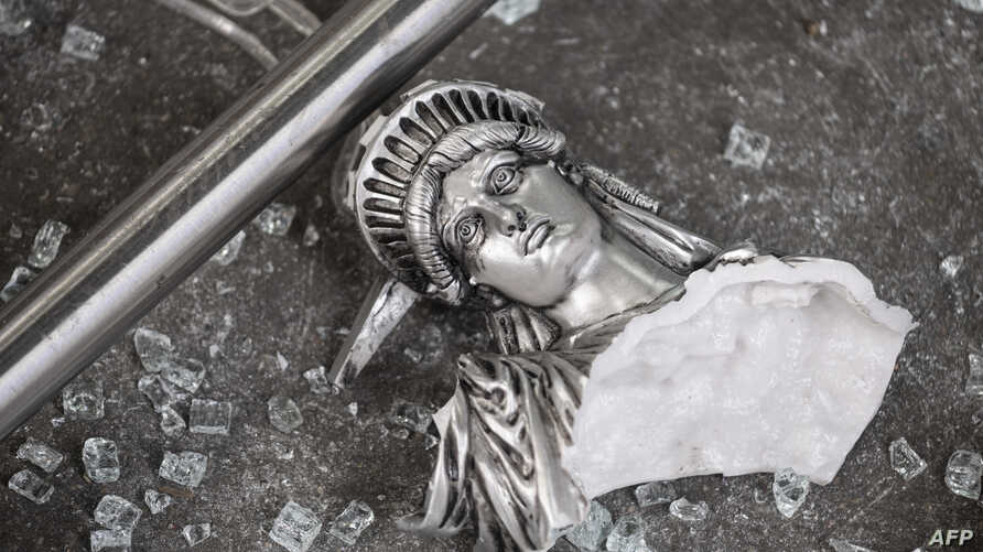 A broken Statue of Liberty figure is seen between glass shatters outside a looted souvenir shop after a night of protests over the death of African-American George Floyd in Minneapolis, in Manhattan in New York City, June 2, 2020.