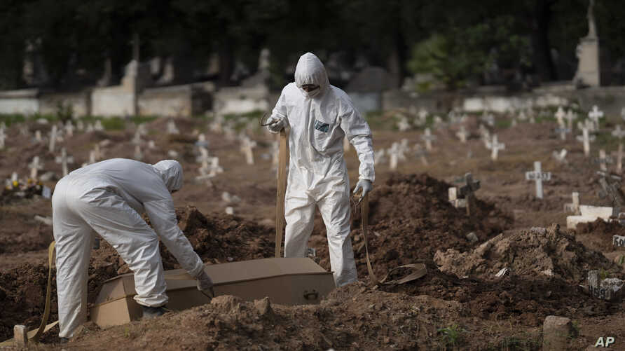 Cemetery workers in protective clothing bury the coffin of 57-year-old Paulo Jose da Silva, who died from the new coronavirus, in Rio de Janeiro, Brazil, June 5, 2020.