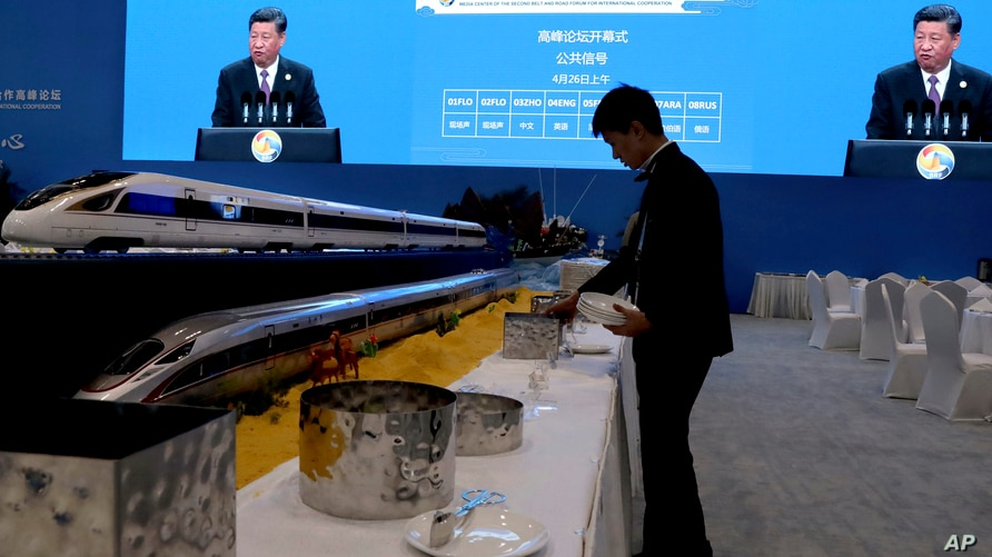FILE - A waiter prepares for lunch next to model high speed trains and screens live broadcasting Chinese President Xi Jinping opening the Second Belt and Road Forum in Beijing, April 26, 2019.