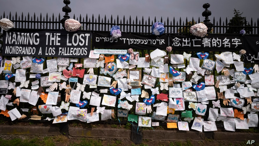 FILE - A fence outside Brooklyn's Green-Wood Cemetery is adorned with tributes to victims of COVID-19, in New York City, May 28, 2020.