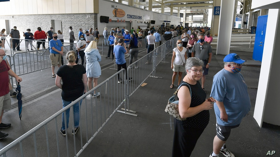 Voters wait in line to cast their ballots in the Kentucky primary at Kroger Field in Lexington, Kentucky, June 23, 2020.